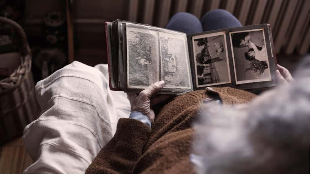 Persona veient àlbum fotogràfic de records