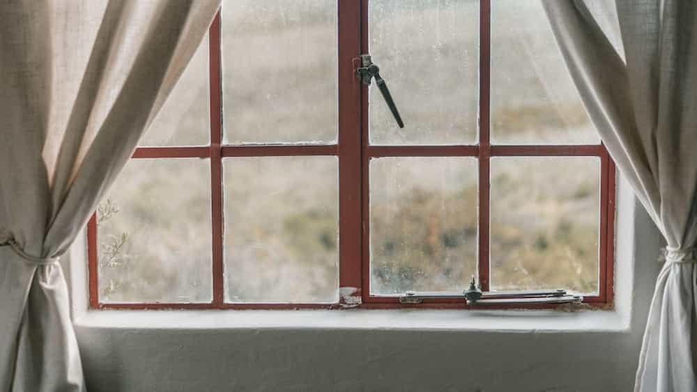 Finestra amb vidres entelats i cortines
