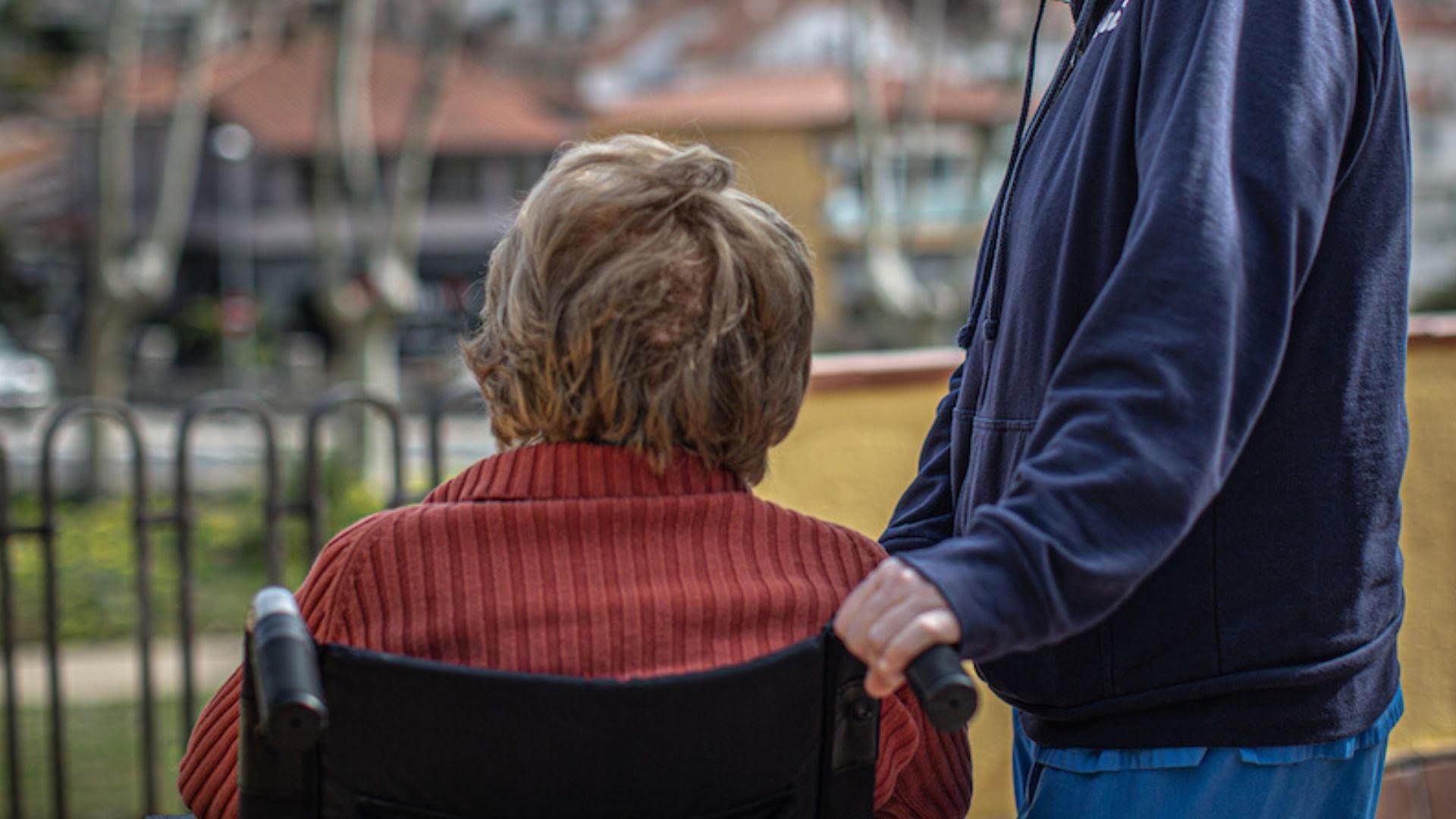 Dona en cadira de rodes acompanyada per un home