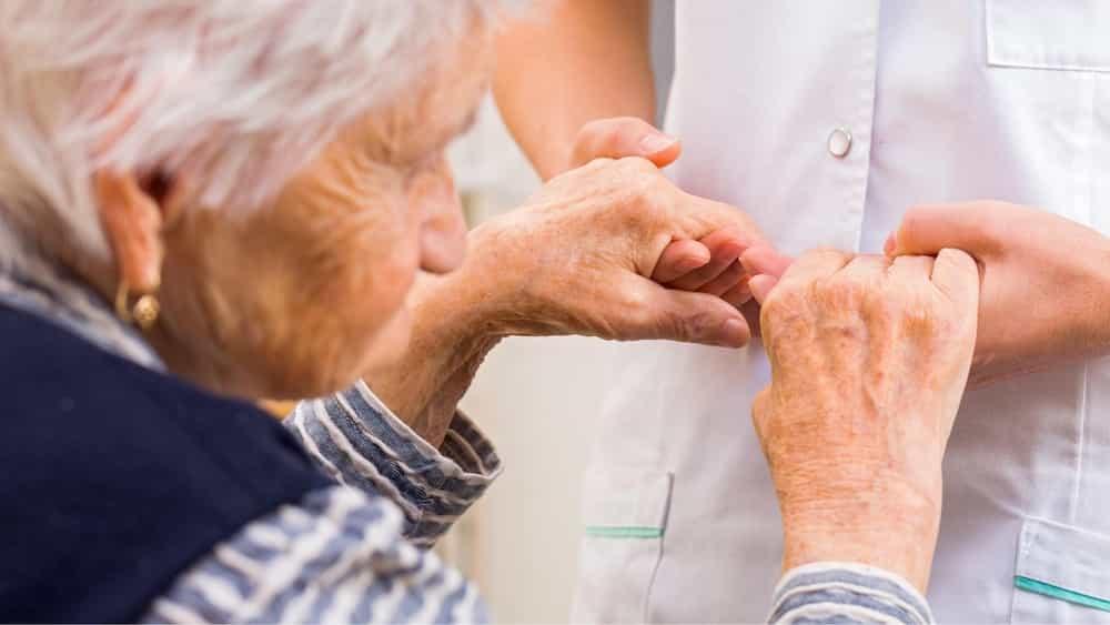 Dona gran agafada a les mans d'una infermera
