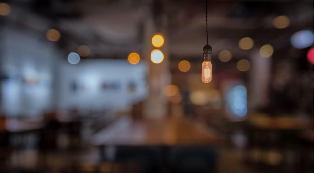 Escena difuminada d'un local amb llums i una bombeta encesa en primer pla