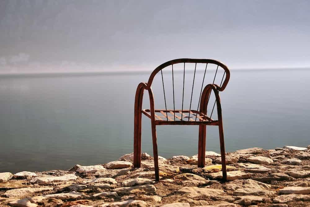 Cadira de metall sola davant el mar