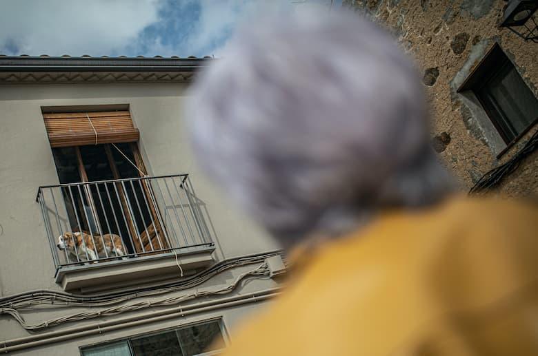 Dona mirant a un gos en que està en un balcó
