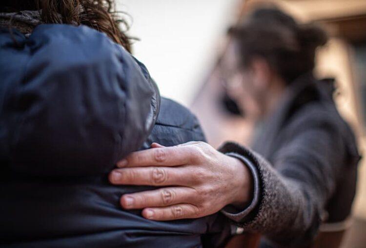 Un home recolza la seva mà sobre l'esquena d'un altre