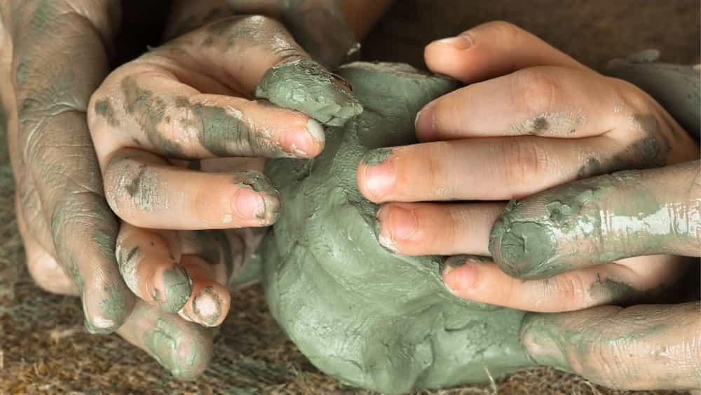 Mans d'un pare ajudant al seu fill a modelar argila