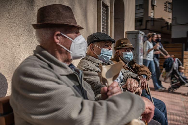 Senyors asseguts en un banc amb mascareta
